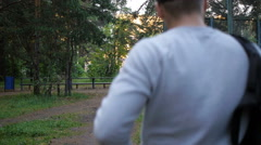 One man walk in wood with bag, back view Stock Footage