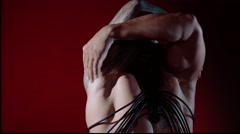 Muscular sexy naked man dancing in the studio on red light background - stock footage