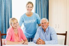 Volunteer taking care of senior couple Stock Photos