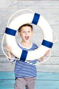 little boy holding a life preserver and screaming - stock photo