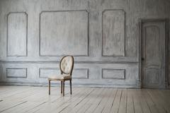 White vintage chair standing in front of a light wall with mouldings on wooden - stock photo