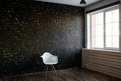 White modern chair and black brick background. Loft style. Minimal chair and - stock photo