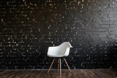 White chair standing in room on brown wooden floor over black brick wall - stock photo