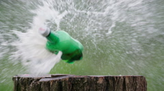 Beer plastic bottle gun shot in native slow motion scene on green background Stock Footage