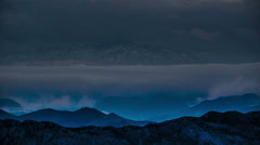 Storm clouds over high mountain peaks surreal blue valley glow time lapse 4k - stock footage