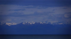 Kyrgyzstan, Issyk Kul lake, clouds and snow covered mountains. 4K time lapse Stock Footage