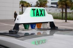 Green taxi sign in France on the car - stock photo