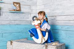 Little girl sitting and holding an anchor Stock Photos