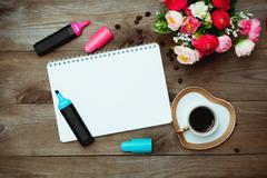 Notepad, cup black coffee and flowers Stock Photos