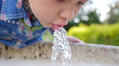 Cute little girl face portrait drink water in a park from drinking fountain slow Stock Footage