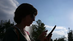 Female silhouette sliding typing smart phone against sun in slow motion Stock Footage