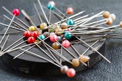 Pins attach round magnetic pincushion on black leather - stock photo