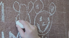 Little girl drawing bee with chalk on blackboard Stock Footage