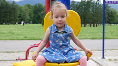Kids on playground for children - little child girl play in a park sit on swing Stock Footage