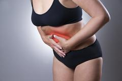 Woman with abdominal pain. Pain in the human body - stock photo