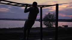 Strong Man doing Pull Ups Outdoor under very Hot Sun in a park Stock Footage
