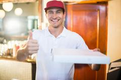 Pizza delivery man holding pizza box gesturing thumbs up - stock photo