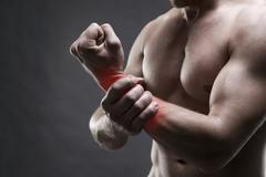Pain in the hand. Muscular male body. Handsome bodybuilder posing on Stock Photos