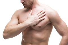 Heart attack. Young muscular man with chest pain isolated on white background Stock Photos