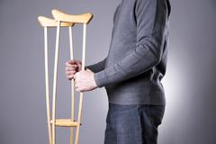 Man on crutches on a gray background Stock Photos