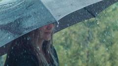 Blonde woman twisting umbrella under rain Stock Footage