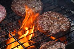 Meat burgers for hamburger grilled on flame grill Stock Photos