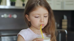 Little girl drinking milk through a straw from a glass Stock Footage