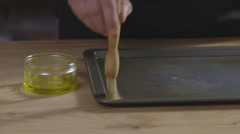 Brushing oil onto a baking tray Stock Footage