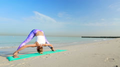 Young woman doing Vinyasa yoga poses by the sea Stock Footage