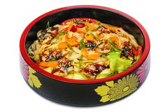 Tagliatelle pasta with smoked eel and vegetables in black bowl isolated on white Stock Photos