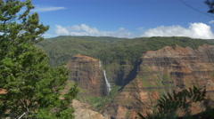 Majestic waterfall running down the magnificent Waimea canyon mountain wall Stock Footage