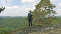 On top of the mountain standing young adult looking over world 4K - stock footage