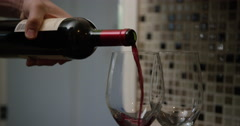 Caucasian hand pours two large glasses of red wine. Slow motion. Stock Footage
