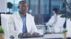 4K Scientist in white coat looking at interactive computer screen in modern lab Stock Footage