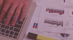 Man working in the evening, compare figures on charts, typing notebook Stock Footage