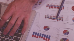 man at work in the evening, home office, with some charts and notebook typing - stock footage