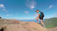 Active young woman walking on path along the mountain ridge with stunning views - stock footage