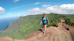 Active young woman walking along the high mountain path with stunning ocean view - stock footage