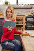 Woman reading a book and eating a cake - stock photo
