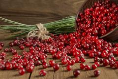 Cranberry is scattered on the wooden table Stock Photos