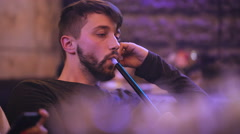 Handsome man smokes hookah in the bar Stock Footage