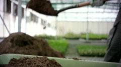 Farm worker pouring soil into wheelbarrow. - stock footage