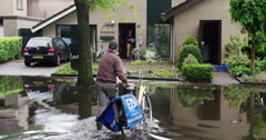 extreme rain netherlands with cyclist walking towards house owner, 4K - stock footage
