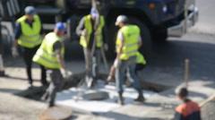 Road workers repair the road, blurred defocused background Stock Footage