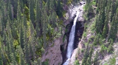 Aerial video of high waterfall in mountain spruce forest. Kyrgyzstan - stock footage