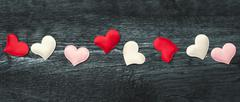 Red hearts on the dark boards Stock Photos