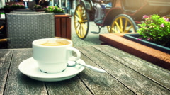 Cup of coffee on wooden table. Bruges cityscape with horse drawn carriage - stock footage