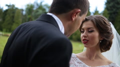 Beautiful happy brunette bride with red lips telling something to her groom Stock Footage