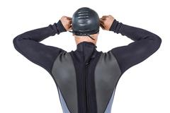 Rear view of swimmer in wetsuit wearing swimming goggles on white background - stock photo
