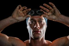 Portrait of swimmer wearing swimming goggles on black background Stock Photos